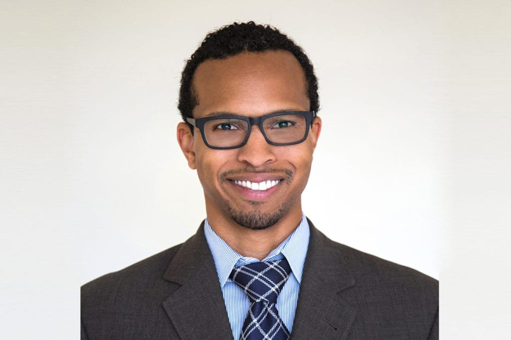 Headshot of black-owned business co-founder Biffrey Braxton, man in suit with glasses smiling.