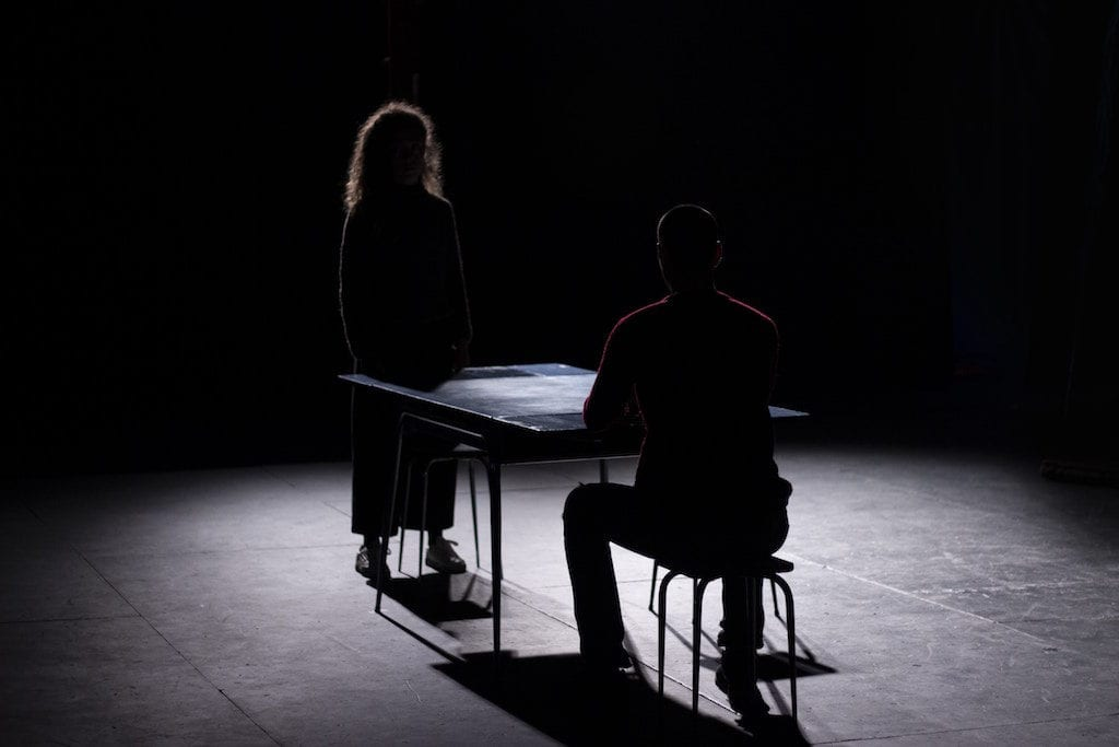 On a very dark stage, a man sits at a table and a woman stands across from him. The floor is illuminated but their faces are not visible.