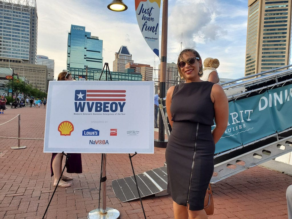 Woman in black dress and sunglasses standing to the right of a sign with the letters WVBEOY and logos in Baltimore's Inner Harbor.