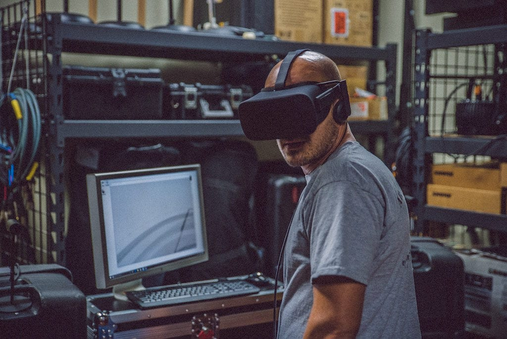 Man in t-shirt wearing virtual reality headset looking at the camera. Standing in front of a computer in an industrial warehouse space.