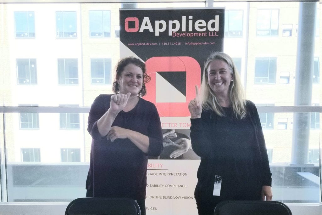 "Two women standing inside in front of a sign that says ""Applied Development."" They are using American Sign Language to sign ""Hi"""