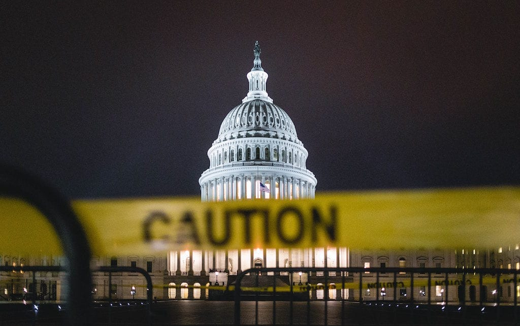 US Capitol building at night with slightly out of focus yellow caution tape in the foreground.