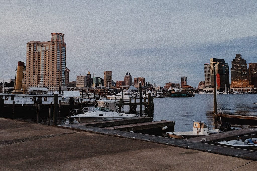 View of Baltimore's Inner Harbor taken from the waterfront. Boats and tall buildings in view.