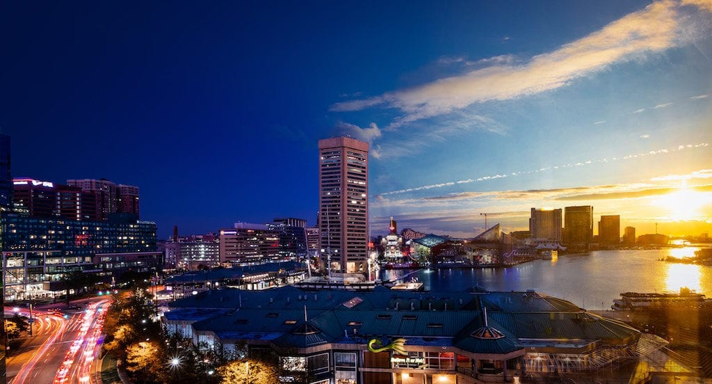 View of Baltimore's Inner Harbor during sunset with World Trade Center, Aquarium, and downtown buildings visible.