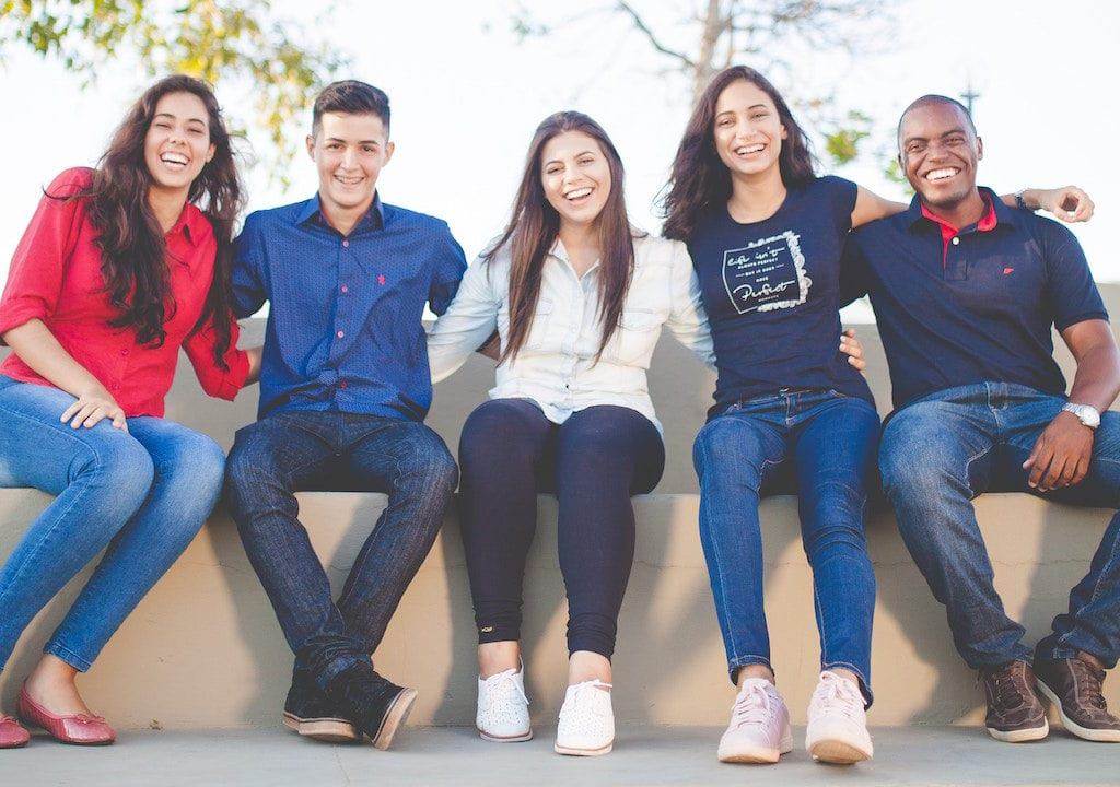 Five people sitting on a bench with their arms around each other smiling