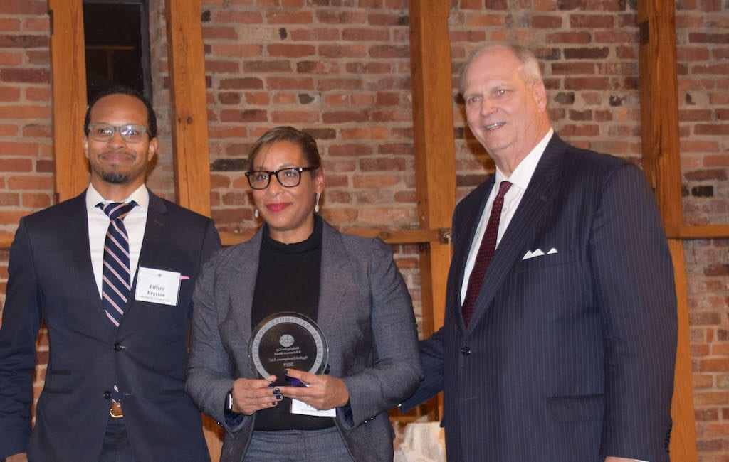 African American man with glasses, African American woman with glasses, and white man posing for the camera at a formal event. Woman holds an award.