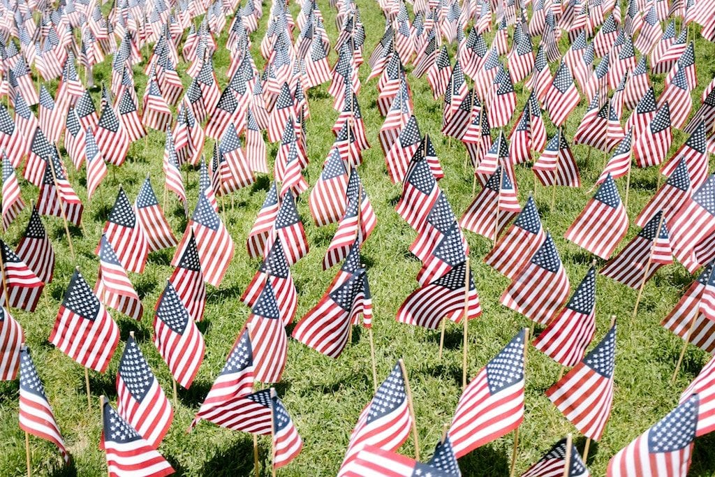 Many small American flags planted on a green field.