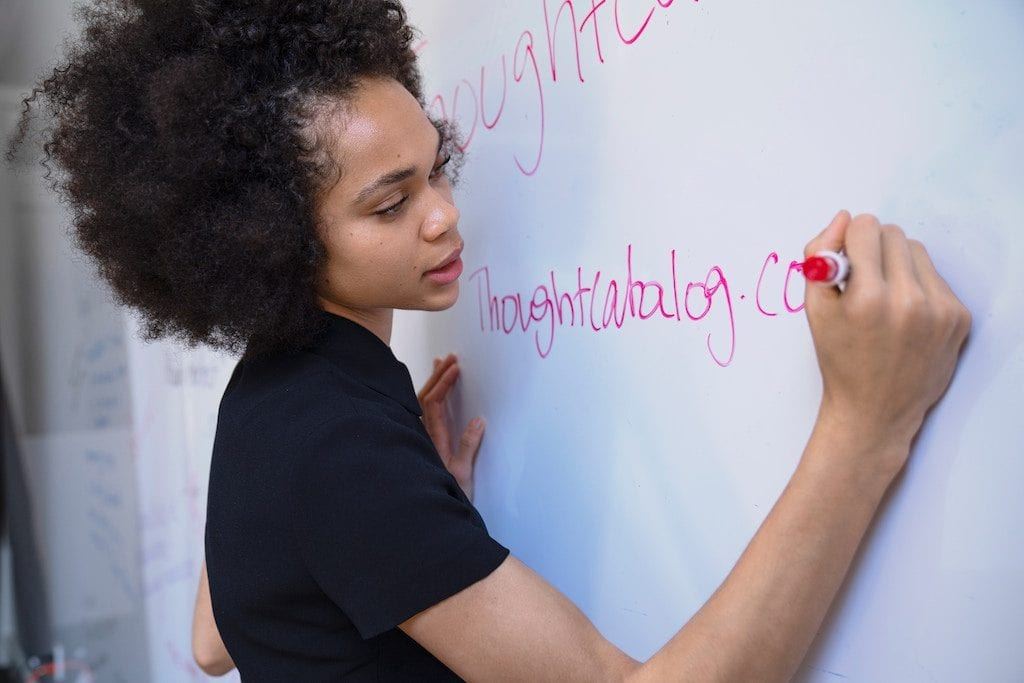 Photograph of a light-skinned African American woman writing in pink marker on a white board.